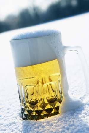 single beer: A glass of beer sitting in snow