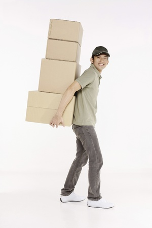 carrying: Man carrying a stack of packages Stock Photo
