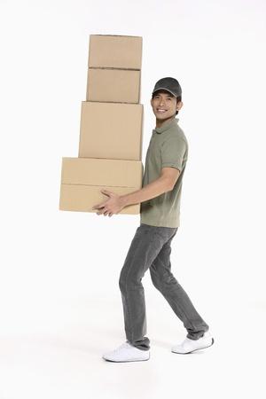 boite carton: Homme transportant une pile de paquets Banque d'images