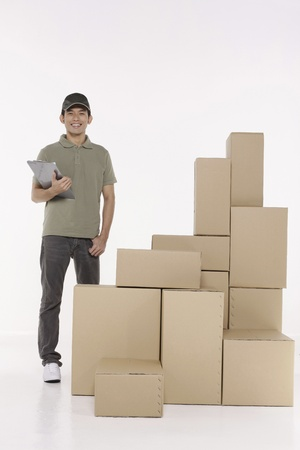 Man with clipboard standing next to a stack of packages photo