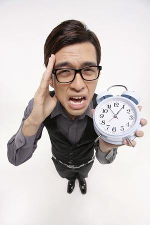 Businessman crying while holding alarm clock photo