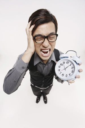 Businessman screaming while holding alarm clock photo