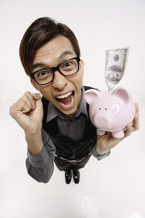 Businessman cheering while holding piggy bank with money photo