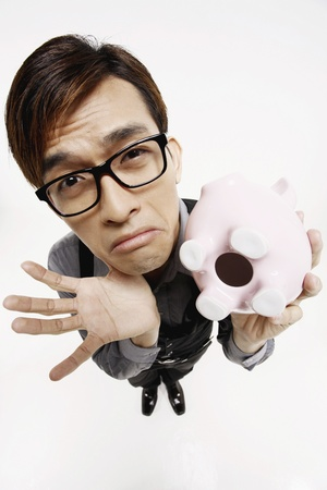 frowning: Businessman with empty piggy bank looking sad Stock Photo