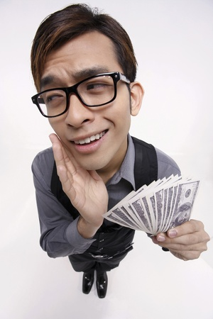 business decisions: Businessman daydreaming while holding money