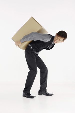 man carrying box: Businessman carrying heavy box
