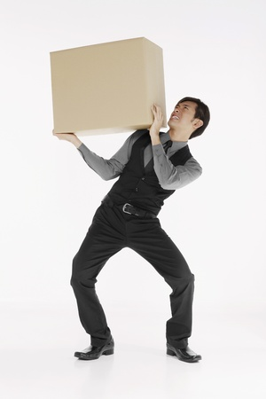 Businessman carrying heavy box Stock Photo - 10057666
