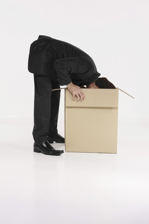 Businessman looking into a box photo