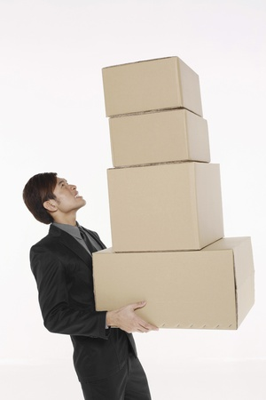 man carrying box: Businessman with a stack of boxes Stock Photo