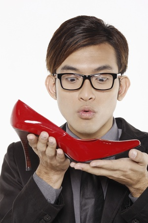 Businessman looking at red stiletto shoe photo