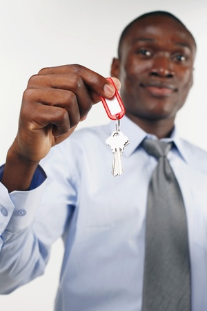 ownership and control: Businessman holding out set of keys