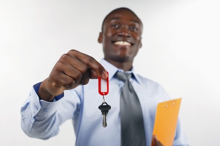 ownership and control: Businessman holding out a key Stock Photo