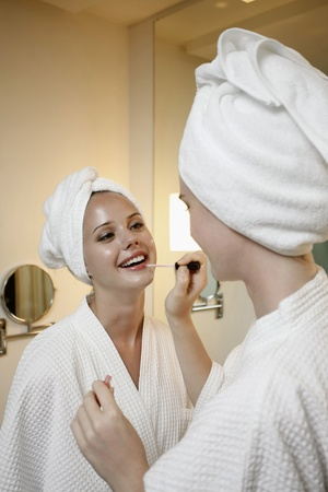 Woman applying make-up for her friend photo