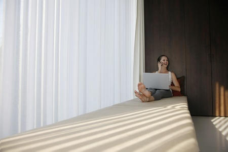 Woman using laptop while talking on the phone Stock Photo - 10572030
