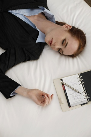 Businesswoman lying down on bed with organizer beside her photo