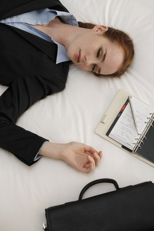 Businesswoman lying down on bed with organizer and briefcase beside her photo