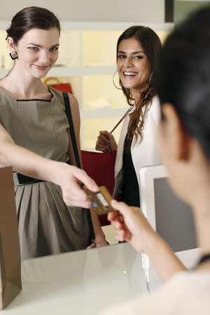 Woman handing credit card to cashier while her friend looks on Stock Photo - 10572663