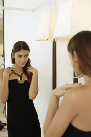 Woman trying on necklace in front of mirror Reklamní fotografie