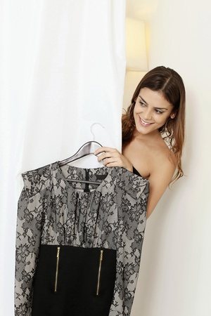 coathanger: Woman trying on dress in fitting room Stock Photo