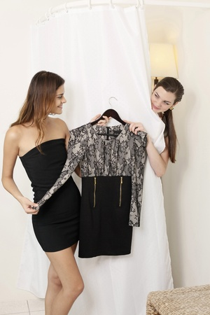 fitting room: Woman passing a dress to her friend in the fitting room Stock Photo