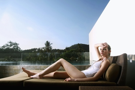 Woman in bikini sitting on lounge chair photo