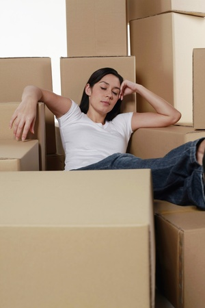 Woman sleeping with cardboard boxes around her photo