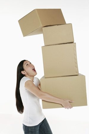 Woman carrying stack of boxes