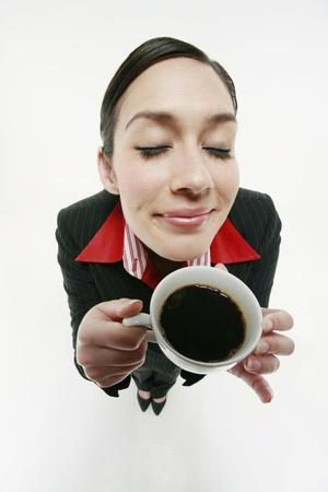personas tomando cafe: Empresaria con una taza de caf� Foto de archivo