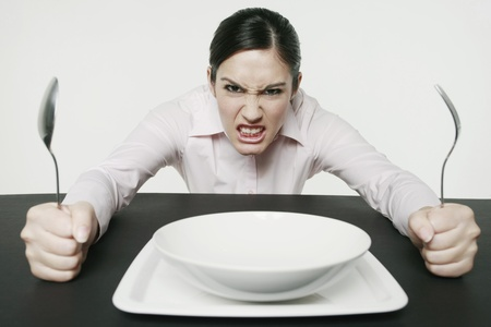 Businesswoman sitting at table looking angry