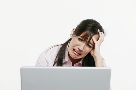 Businesswoman looking stressed while using laptop photo