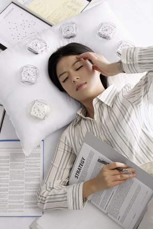 Businesswoman sleeping with alarm clocks around her head photo
