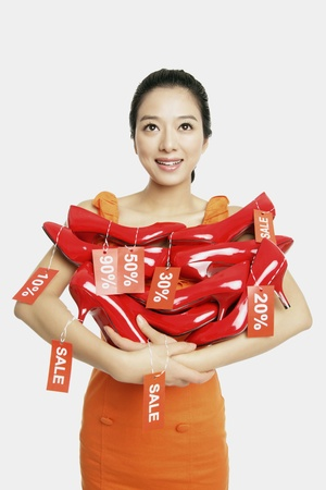 excess: Woman holding red stilettos with sale labels Stock Photo