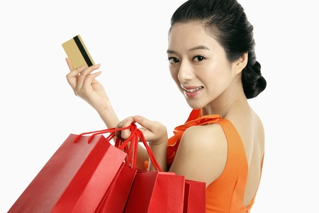 Woman with shopping bags holding up credit card Stock Photo