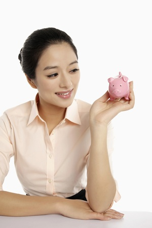 Businesswoman holding a small piggy bank