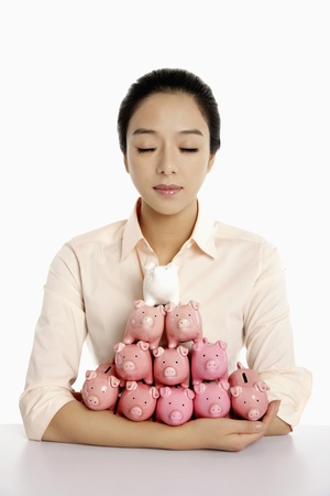 armful: Businesswoman with an armful of piggy banks