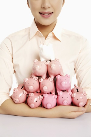 Businesswoman with an armful of piggy banks photo