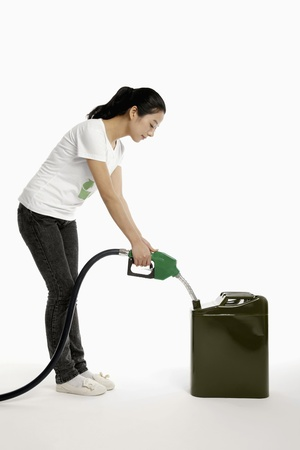 petrol can: Woman holding a petrol pump filling a gas can Stock Photo