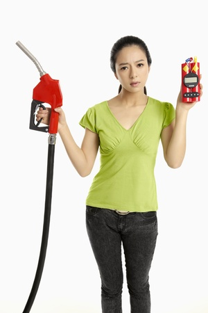 petrol bomb: Woman holding a red petrol pump and a time bomb Stock Photo