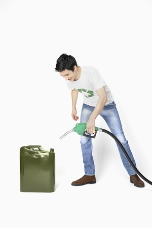 gas can: Man holding a petrol pump filling a gas can Stock Photo