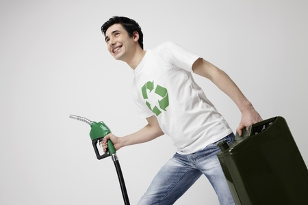 gas can: Man holding a petrol pump and a gas can