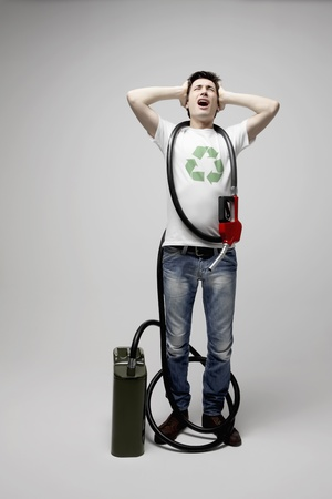 gas can: Man with gas pump and gas can screaming while covering his ears Stock Photo