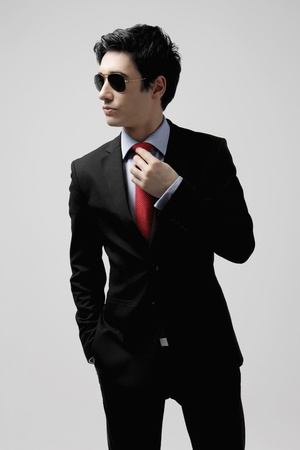 Businessman with sunglasses adjusting his tie photo