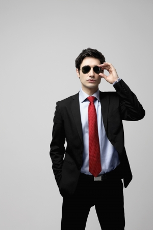 Businessman adjusting his sunglasses Stock Photo