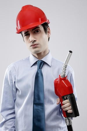 Businessman with hard hat holding fuel pump photo