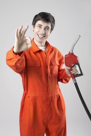 Man in coveralls holding fuel pump and showing OK sign photo