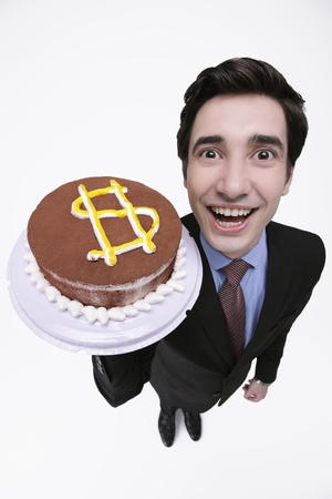 Businessman holding cake with dollar sign photo