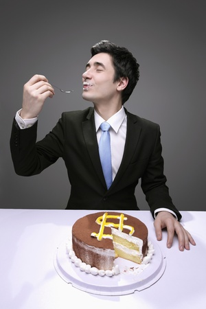 messily: Businessman messily eating a cake with a dollar sign. Stock Photo