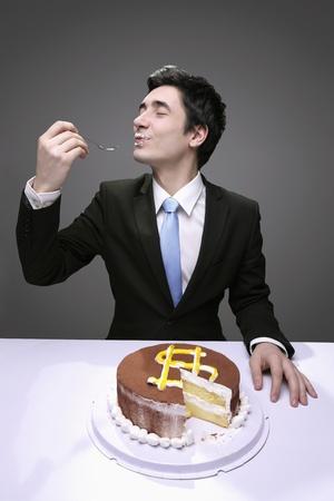 signo pesos: Empresario desordenadamente comer una torta con un signo de d�lar.