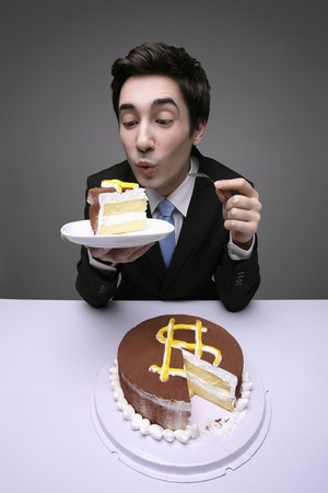 Caucasian businessman holding up a slice of cake taken from a chocolate cake with a dollar sign icing on it. photo