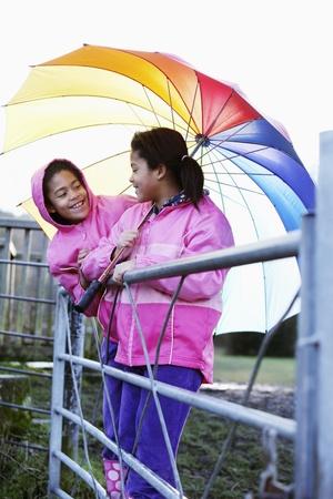 Girls sharing an umbrella photo